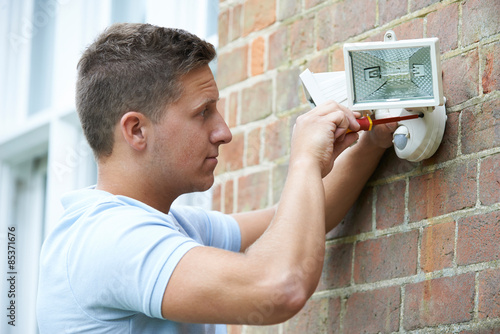 Obraz Security Consultant Fitting Security Light To House Wall - fototapety do salonu