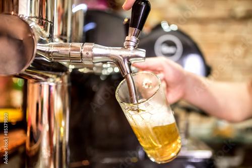 Barkeeperhand am Bierhahn, der ein Entwurfslagerbier gießt, das in einem Restaur Fototapete