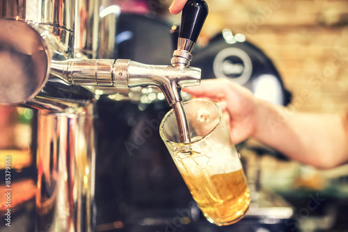 Fotografía  barman hand at beer tap pouring a draught lager beer serving in a restaurant or
