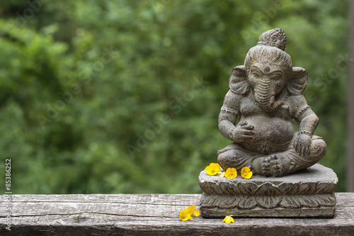 stone statue of Ganesha with yellow flowers and green blurry nat