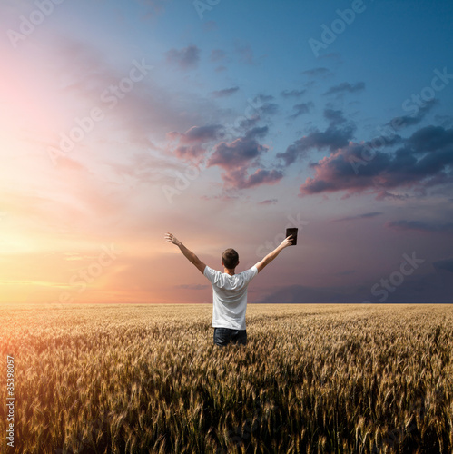 Valokuva  man holding up Bible in a wheat field
