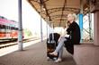 junge Frau mit Handy wartet auf ihren Zug