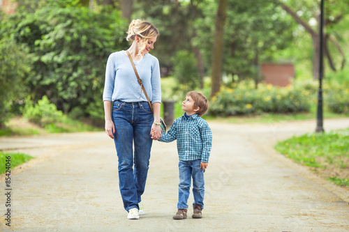 Fototapeta Young mother and her cute little son walking in a park obraz