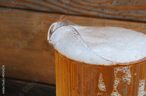 Valokuva  Closeup of Beer Pitcher with Wood Background