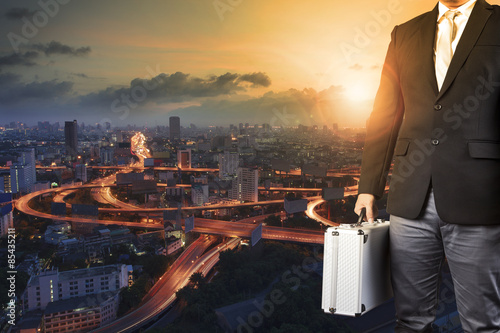 Fotografía  business man and metal briefcase luggage in hand standing agains