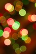 Brightly colored Christmas lights on a Christmas tree. Forced out of focus.