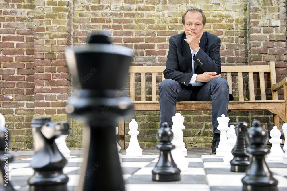 Fototapeta Thinking man sitting at a life sized outdoor chess board