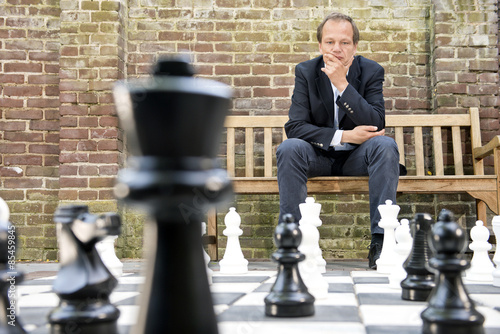 Thinking man sitting at a life sized outdoor chess board