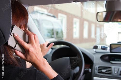 Fototapety, obrazy: Frau telefoniert am Steuer