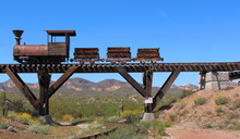Old Wild West Train With Mining Carts Passing Over An Old Wooden Bridge With Mountains, Cactus And Wild Flowers In Background