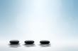 Zen concept. Black spa stones on blue background.