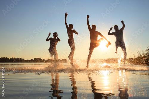 Fotografie, Obraz  Glückliche junge Menschen laufen und springen am See beim Sonnenuntergang