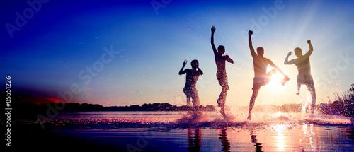 Glückliche junge Menschen laufen und springen am See beim Sonnenuntergang #85551226