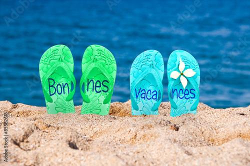 Bonnes vacances écrit sur des tongs sur une plage