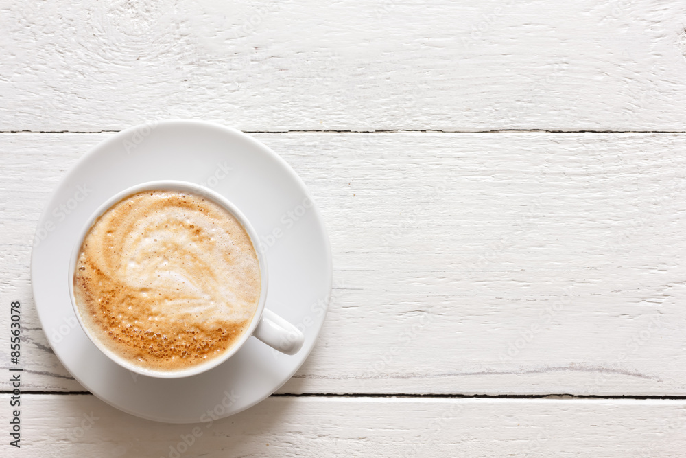 Cappuccino in cup on rustic painted wood. From above.