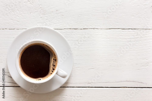Black coffee in cup on rustic painted wood. From above.
