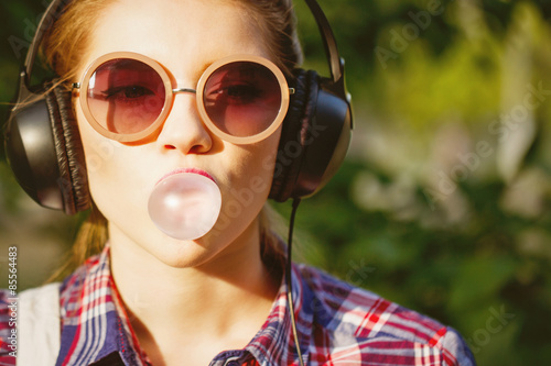 Papiers peints Magasin de musique Hipster girl listening to music on headphones and chews the cud.