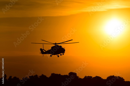 Foto  silhouette of military helicopter at sunset