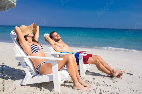 Happy couple relaxing on deck chair at the beach