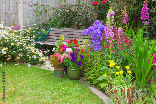 Fotobehang Tuin Cottage garden with bench and containers full of flowers