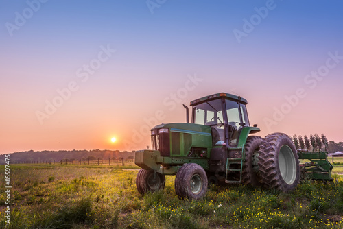 Tractor in a field on a Maryland farm at sunset плакат