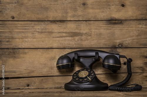 Foto  Altes Telefon mit Schnur auf Holz Hintergrund