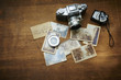 Vintage photo camera with old photographs on a wooden table