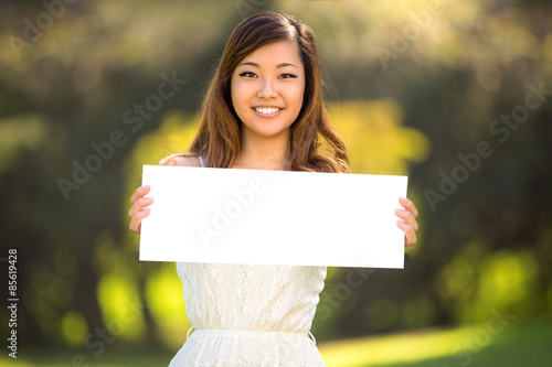 Fotografering  A beautiful young adult woman holding a blank white sign card outdoors smiling c