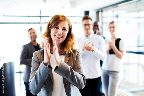 Fotografía  White female executive standing in front of colleagues clapping