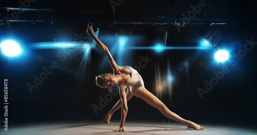 Slika na platnu Ballerina posing on stage against spotlights