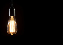 A Classic Edison Light Bulb On Black Background With Space For Text