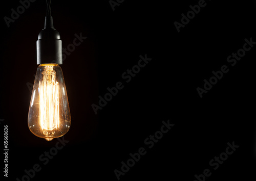 Photo  A classic Edison light bulb on black background with space for text