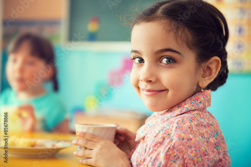 Photo  Cute hispanic girl drinking milk at school