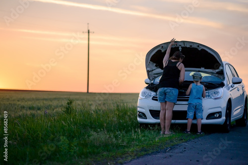 Fotografia, Obraz  Mother and Son Repairing Something on their Car