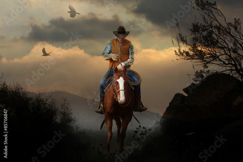 Obraz na plátne A mountain cowboy rides to the peak of a mountain with a beautiful cloudy sunset in the background with birds and crows flying above
