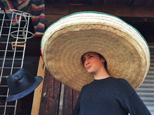 Girl Wearing A Giant Sombrero In A Market, Mexico