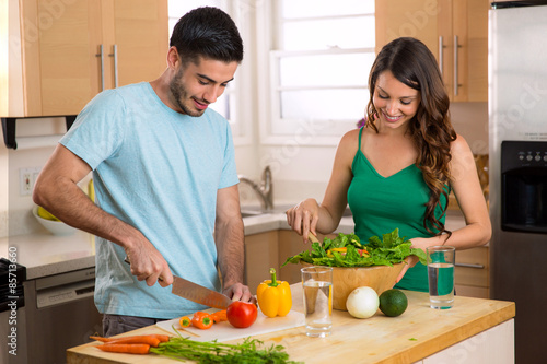 Fotografie, Obraz  Attractive man and woman prepping low calorie dinner in kitchen very health cons