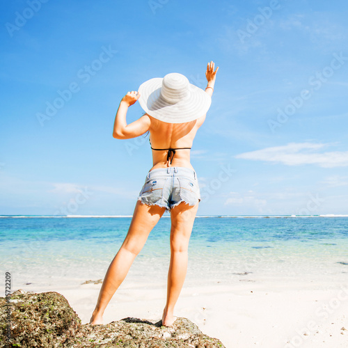young skinny caucasian girl with tan stays on the rock facing buy