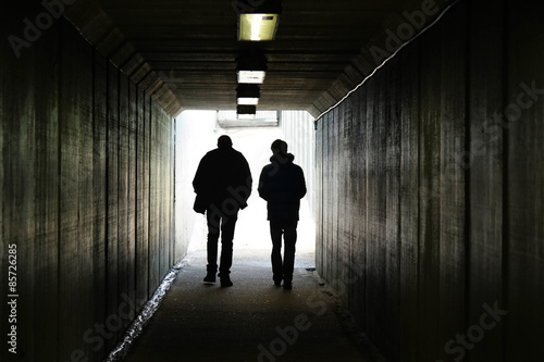 Papiers peints Tunnel Two persons walk to the light in the end of the tunnel.