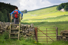 Hiker Crossing A Stile
