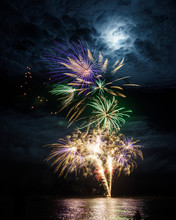 Firework Explosion Over The Sea With The Full Moon And Thin Cloud
