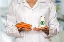 Young Doctor Holding Carrots And Bottle Of Pills With Vitamin A And Compare Them