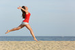 Teen girl in red jumping happy on the beach