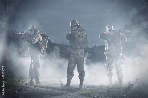 Men with rifle aiming in battlefield at night Canvas Print