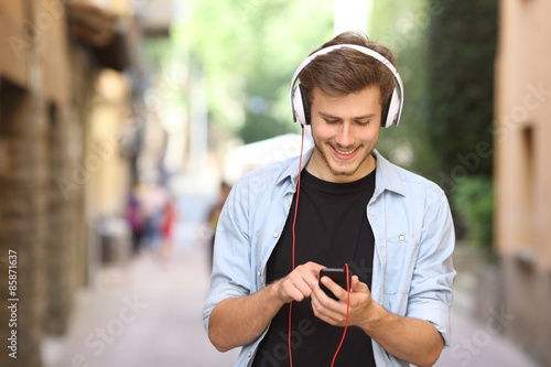 Photo  Guy walking and using a smart phone with headphones