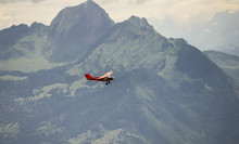 A Small Red Airplane Flying Over The French Alps