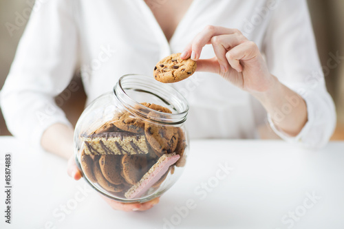 Fototapeta close up of hands with chocolate cookies in jar