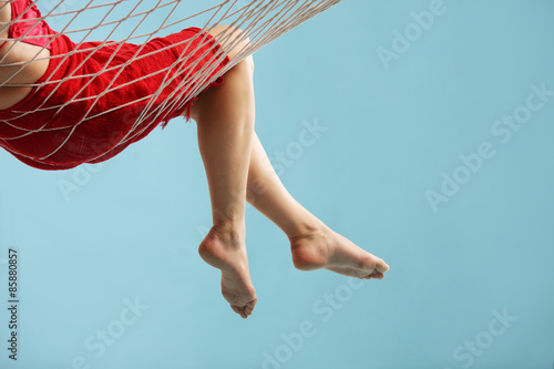 Fotografie, Obraz  Close-up on the legs of woman lying in a hammock
