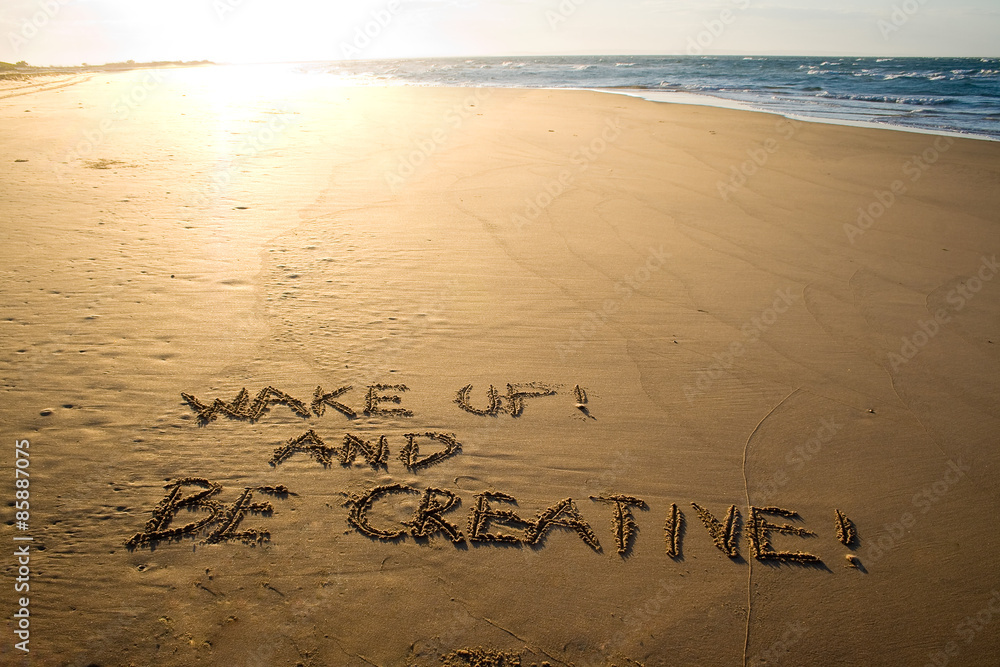 Photo  Wake up and be creative! Creative motivation concept written in the sand at the beach