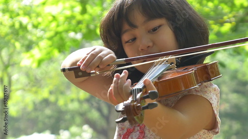 Photo  Little Asian girl playing violin in the park